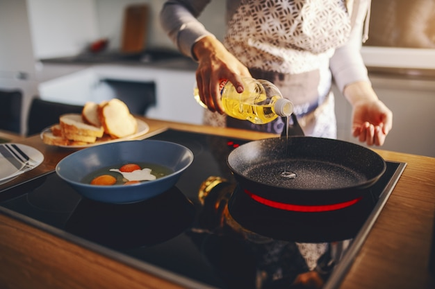 Vrouw in schort olie in de koekenpan gieten terwijl je naast de kachel