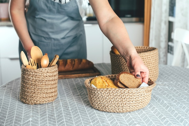 Vrouw in schort snijdt zelfgemaakt glutenvrij brood in keukentafel met meer keukengerei close-up