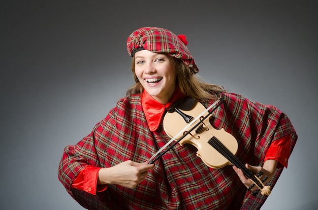 Vrouw in schotse kleding in muzikaal concept