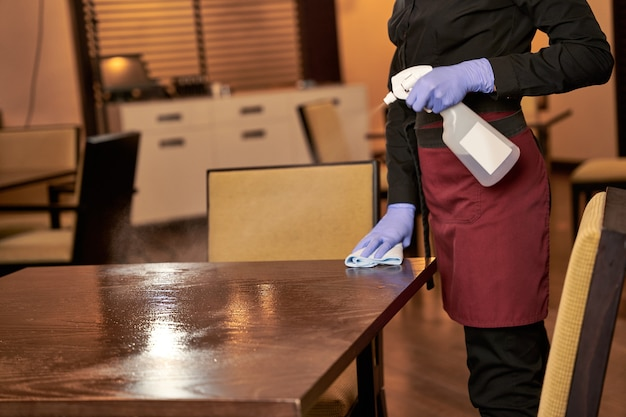 Vrouw in serveersteruniform die rechts van een houten tafel blijft en deze afveegt met een doek en schoonmaakmiddel