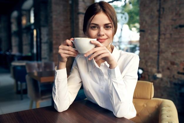 Vrouw in shirt aan tafel in café