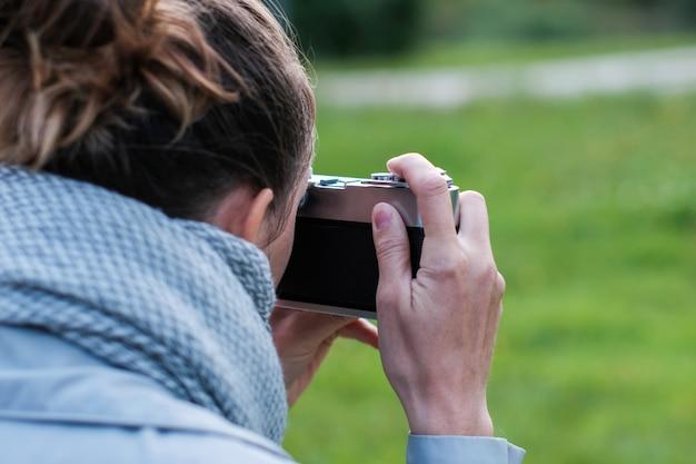 Vrouw in sjaal die foto's met retro fotocamera neemt op straat
