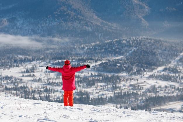 Vrouw in ski-uitrusting neemt de energie van de zon op met haar armen gestrekt tegen de achtergrond van blauwe bergketens. jack met capuchon, rode broek. gezonde levensstijl. sport concept. selectieve aandacht.