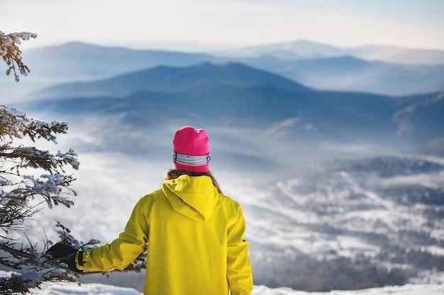 Vrouw in ski-uitrusting vormt tegen de achtergrond van verre blauwe bergen en sparren. geel of mosterd jasje met capuchon, gebreide muts. achteraanzicht. gezonde levensstijl. sport concept. selectieve aandacht.