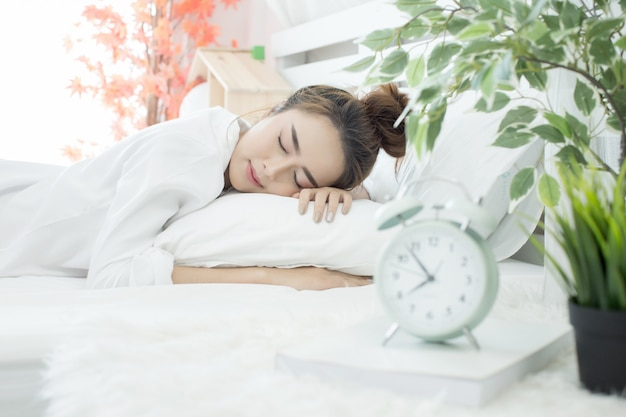 Vrouw in slaap in bed terwijl haar alarm de vroege tijd thuis in de slaapkamer laat zien