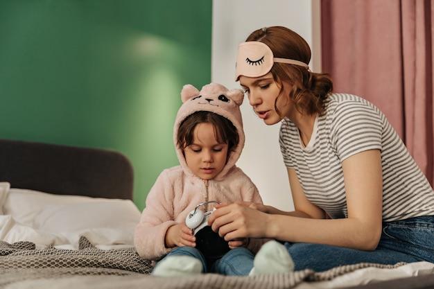 Vrouw in slaapmasker leert haar dochter in schattige pyjama's hoe ze de wekker moet starten.