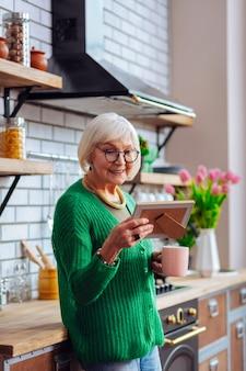 Vrouw in smaragdgroen vest en stijlvolle bril die vrolijk foto's bewondert