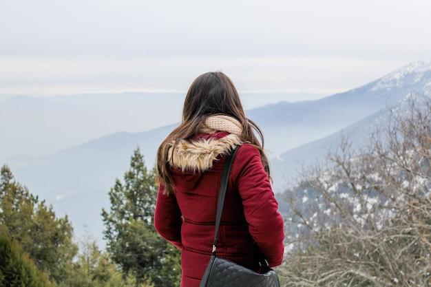 Vrouw in sneeuw met bomen en bergen op de achtergrond