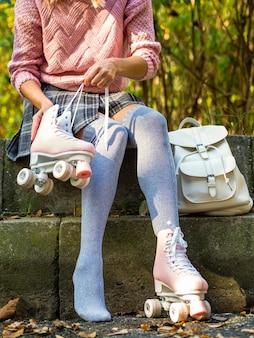 Vrouw in sokken met rolschaatsen en rugzak