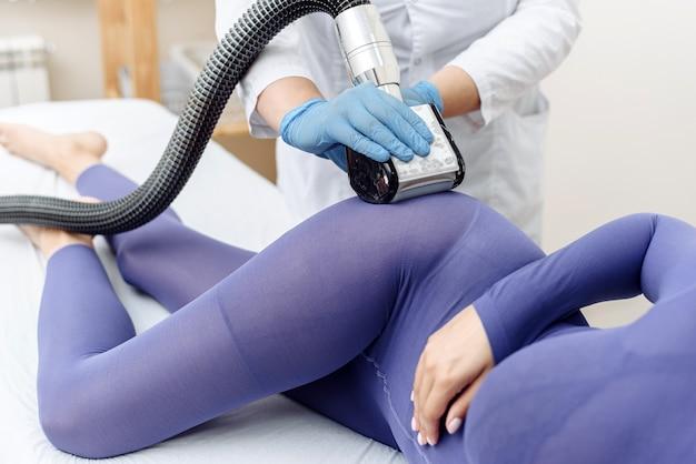 Vrouw in speciaal paars pak anti cellulitis massage krijgen in een spa salon. lpg-massageprocedure. handen van therapeut lipomassage tool te houden.