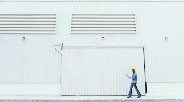 Vrouw in spijkerbroek dragen gele veiligheidshoed voorzijde van metalen plaat muur op bouwplaats