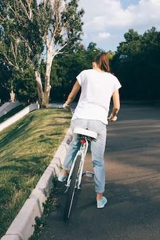 Vrouw in spijkerbroek en een t-shirt zit op een fiets in het stadspark