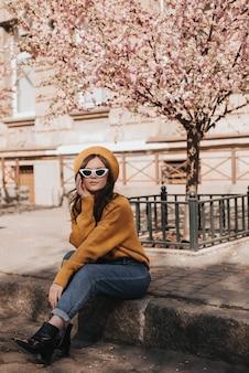 Vrouw in spijkerbroek en trui rust op de stoeprand tegen de achtergrond van sakura. portret van dame in stijlvolle outfit in parijse stijl genieten van lenteweer