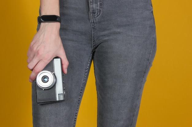Vrouw in spijkerbroek heeft een retro filmcamera op een gele achtergrond.