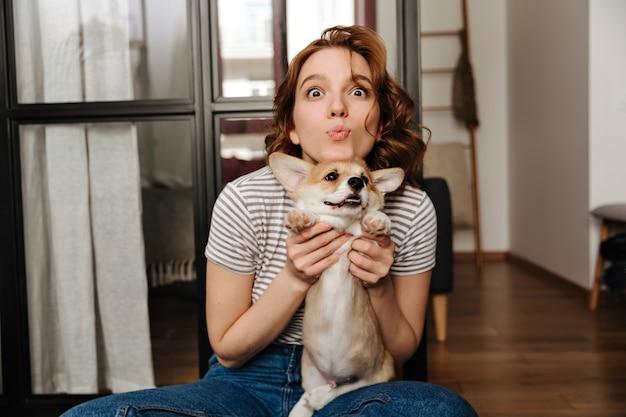 Vrouw in spijkerbroek maakt grappig gezicht, plezier en knuffels corgi.