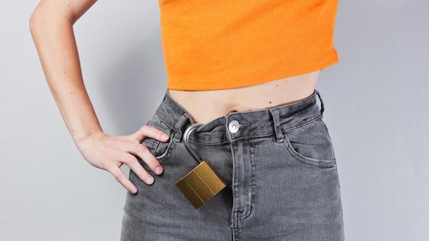 Vrouw in spijkerbroek met een slot eraan
