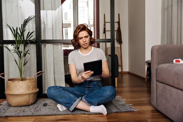 Vrouw in spijkerbroek zit op de vloer in appartement en kijkt met misverstand naar haar tablet.