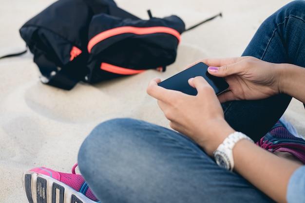 Vrouw in spijkerbroek zittend op het strand zand in kleermakerszit en met behulp van een mobiele telefoon met een touchscreen