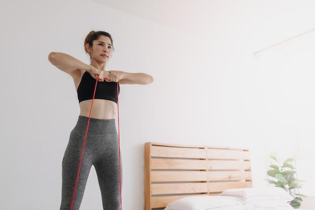 Vrouw in sport draagt weerstandsband rechtop rijtraining in slaapkamer