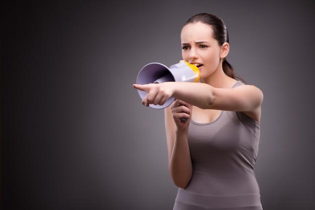 Vrouw in sportenconcept met luidspreker