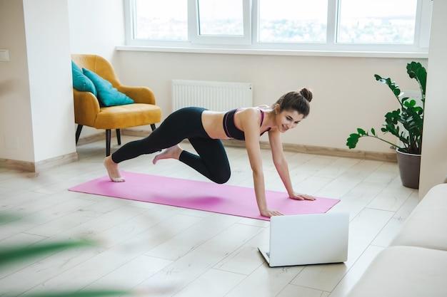 Vrouw in sportieve kleding thuis met behulp van laptop vrouw online uitrekken en yoga fitness oefening doen...