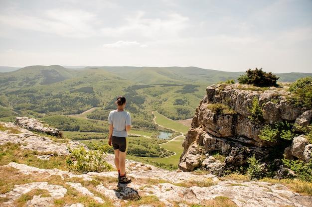 Vrouw in sportieve uniform en sneakers staat op bergen piek
