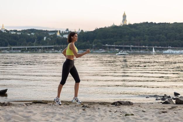 Vrouw in sportkleding bij zonsondergang op het stadsstrand hardlopen