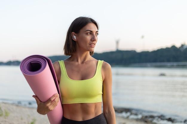 Vrouw in sportkleding bij zonsondergang op het stadsstrand met yogamat en draadloze koptelefoon