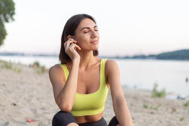 Vrouw in sportkleding bij zonsondergang op het stadsstrand, rustend na het sporten en luisteren naar muziek in draadloze hoofdtelefoons