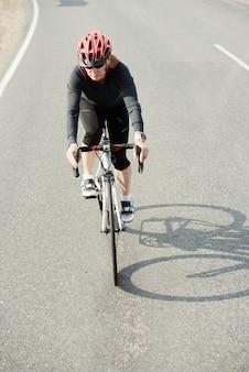 Vrouw in sportkleding die buiten op een fiets rijdt, traint voor triatlon of fietscompetitie
