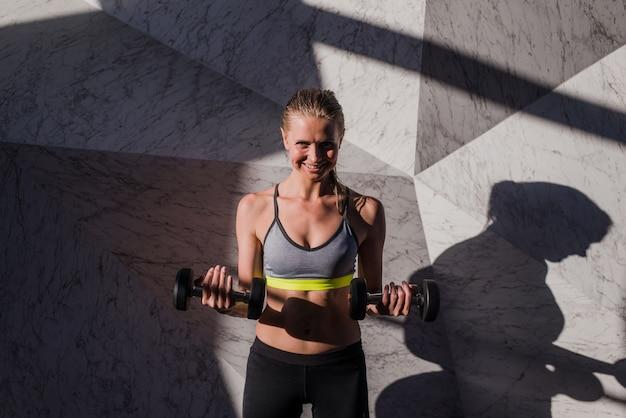 Vrouw in sportkleding die crossfit training met domoor doen