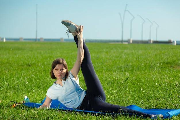 Vrouw in sportkleding die fitnessoefeningen doet op het groene gras