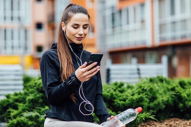 Vrouw in sportkleding die mobiele telefoon gebruikt na het hardlopen in de ochtend.