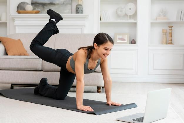 Vrouw in sportkleding die thuis traint