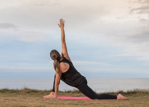 Vrouw in sportkleding die zich uitstrekt buiten op een roze mat met de zee