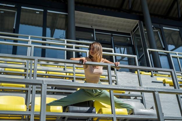 Vrouw in sportkleding die zich uitstrekt voor haar training in het stadion. levensstijl