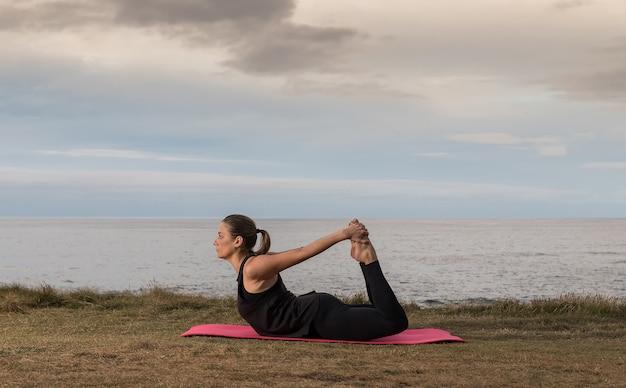 Vrouw in sportkleding doet pilates buitenshuis op een roze mat met de zee