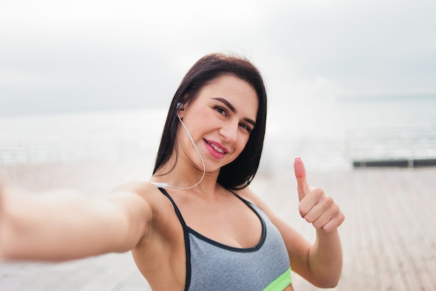Vrouw in sportkleding duim opdagen