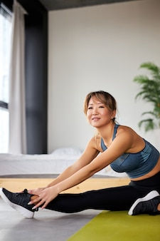Vrouw in sportkleding fitness benen strekken, oefeningen thuis in lichte kamer. sport, gezonde levensstijl en recreatieconcept.