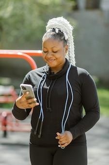 Vrouw in sportkleding met een smartphone