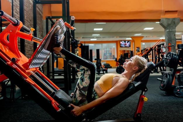 Vrouw in sportkleding oefening op de benen persmachine in de sportschool doet.