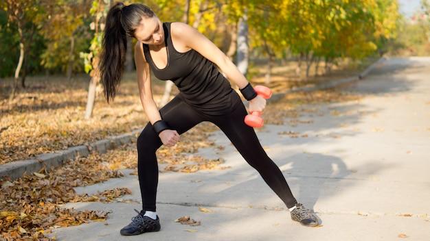 Vrouw in sportkleding voorovergebogen en haar arm opzij te heffen tijdens het trainen met een halter