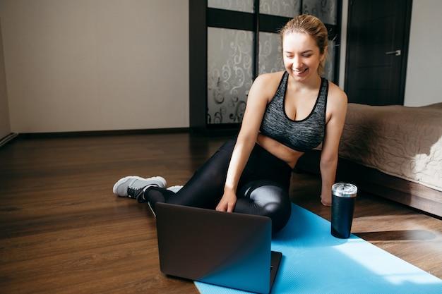 Vrouw in sportkleding zittend op de vloer en het gebruik van een laptop