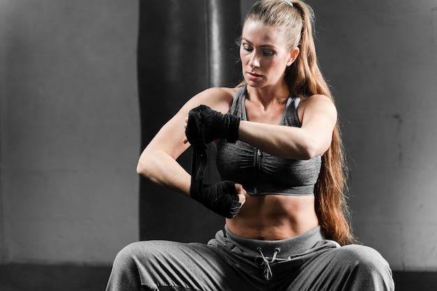 Vrouw in sportkleding zittend op een bankje in de sportschool