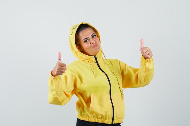 Vrouw in sportkostuum dat dubbele duimen toont en zelfverzekerd, vooraanzicht kijkt.