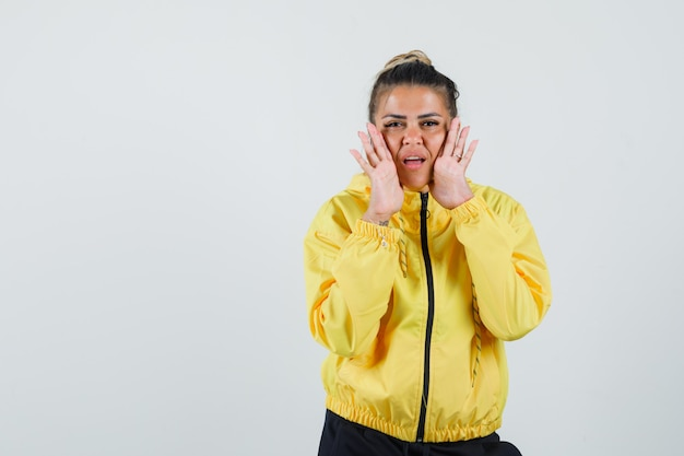 Vrouw in sportkostuum die geheim met handen dichtbij mond, vooraanzicht vertellen.
