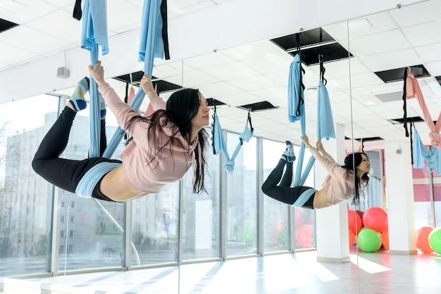 Vrouw in sportschool doen vliegende yoga-oefeningen