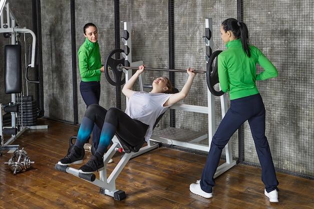 Vrouw in sportschool doet bankdrukken met ondersteuning van twee trainersassistenten