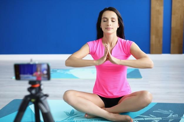Vrouw in sportschool zit in lotushouding voor camera