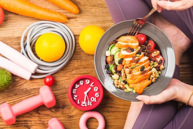Vrouw in sportslijtage die een schotel van verse salade met, gezonde levensstijl, vrouw gezond eten houdt